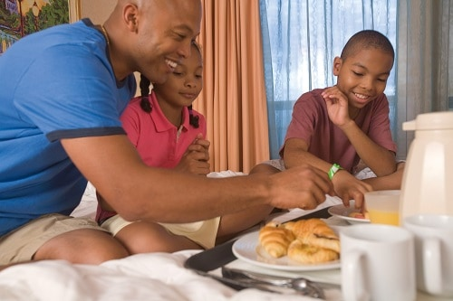 a father and his children having breakfast in a stateroom