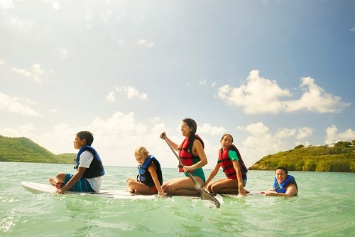 family paddleboarding in the caribbean