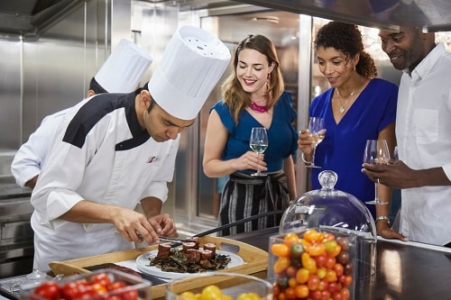 group of friends watching an executive chef prepare his specialty dish
