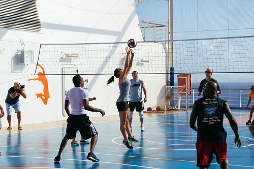 group of people playing volleyball at sportsquare onboard a carnival ship