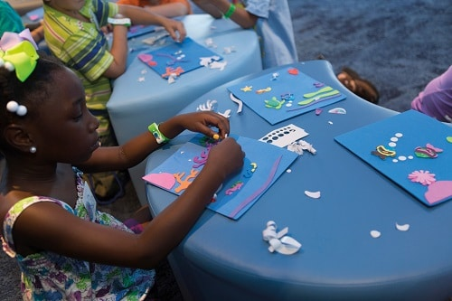 little girl doing crafts on camp ocean