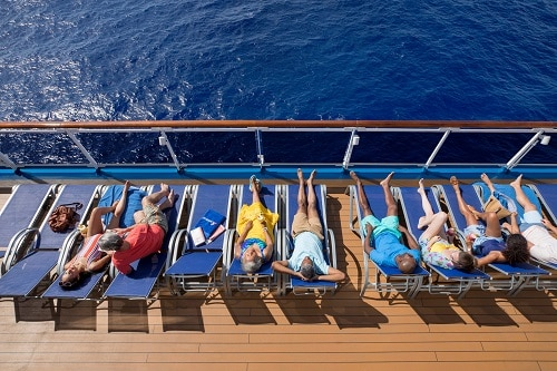 row of people sitting in chairs near the railing of a carnival ship