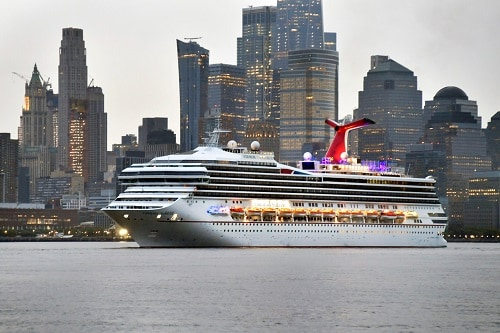 a carnival ship sailing out of new york city at sunset
