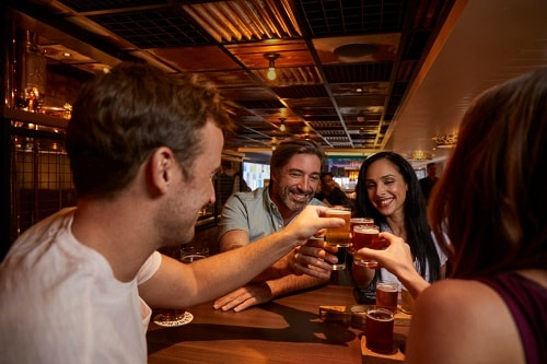 a group of friends enjoying beer at guy's pig and anchor barbeque smokehouse and brewhouse