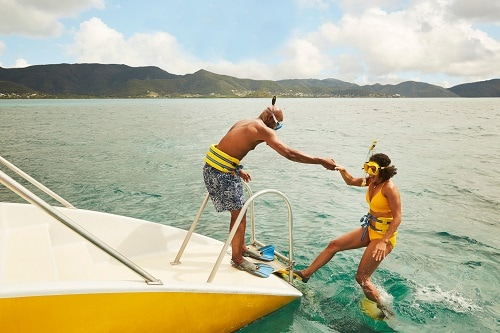 a man helping a woman onto a boat after snorkeling