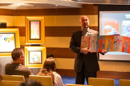 an auctioneer lecturing a crowd on pop art onboard a carnival ship
