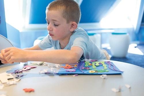 child making crafts at camp ocean