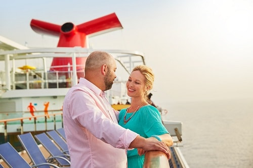 couple standing together at the railing by the funnel onboard a carnival ship
