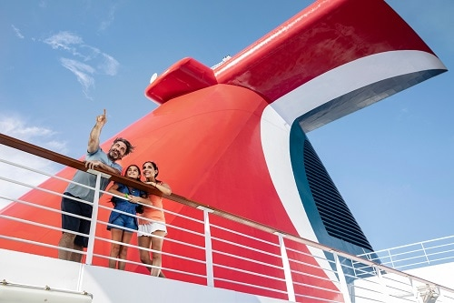 family standing on a dock by the funnel of a carnival ship