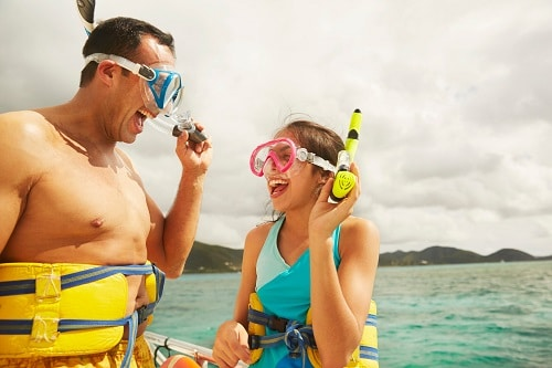 father and daughter laughing together before they go snorkeling