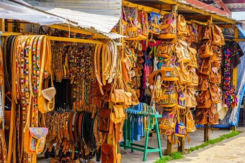 leather belts and backpacks on sale in a market in oaxaca, mexico
