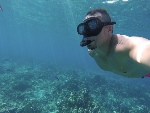 man casually snorkeling through a coral reef
