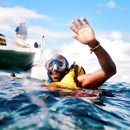 waving into a camera as he finishes snorkeling