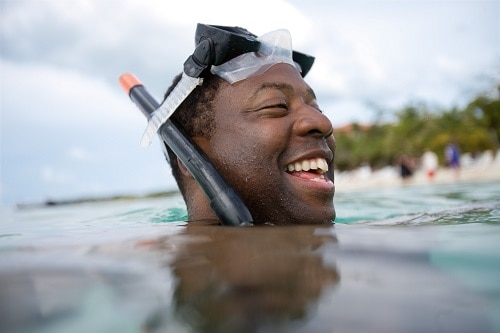 man with snorkel mask coming up from the water after a short dive