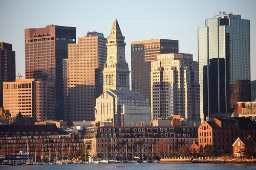 the sun shining on the boston city skyline