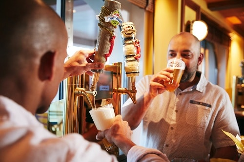 two men drinking thirstyfrog brews from a beer tap