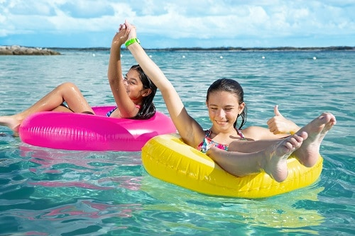 two young girls on the beach in floating tubes