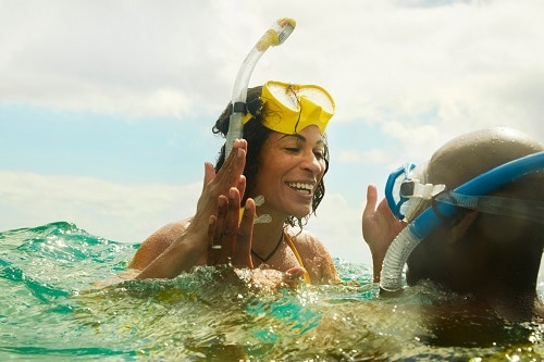 woman expressing excitement with her snorkeling partner above the water