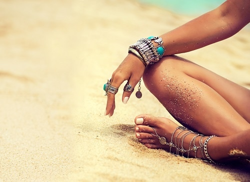 woman wearing silver and blue rings, bracelets and anklets on the beach