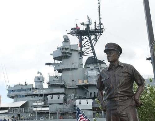 a bronze statue of a soldier in front of the pearl harbor visitors center