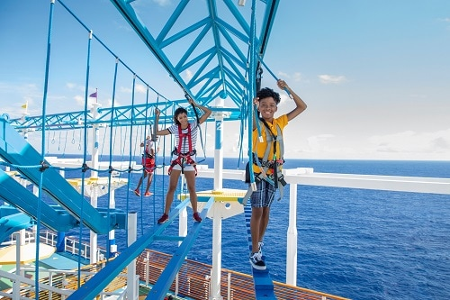 a family making their way through the ropes course onboard a carnival ship