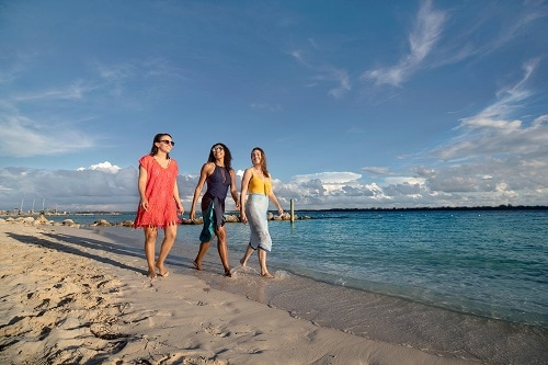 a group of girlfriends walking across the beach together