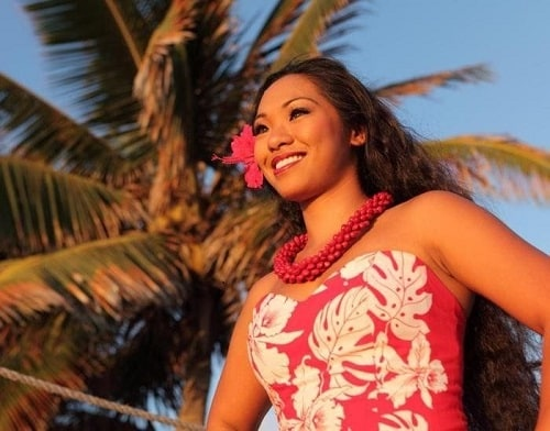 a smiling young hawaiian woman standing behind a palm tree with her hands to her waist