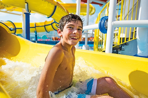 a young boy getting off the twister waterslide