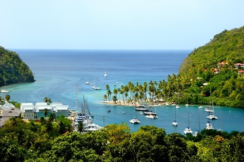 an aerial view of boats sailing around mountains in st. lucia