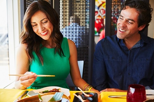 couple enjoying their meal at jiji asian kitchen onboard a carnival ship