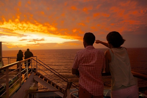 couple looking out to the sunset onboard a carnival ship