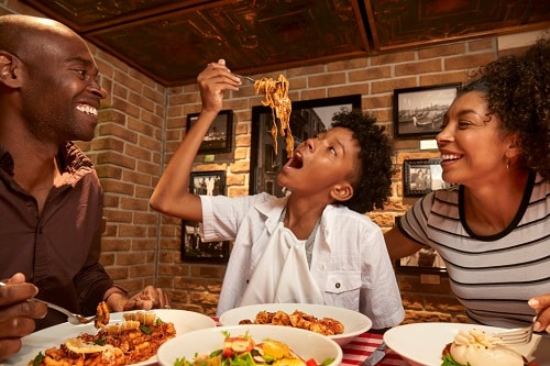 family enjoying an italian dinner at cucina del capitano