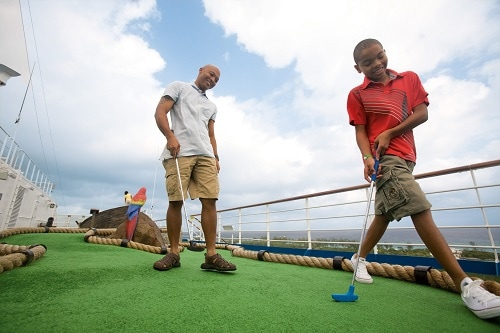 father and son playing mini golf onboard a carnival ship