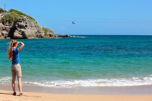 girl looking at someone zip lining in the dominican republic