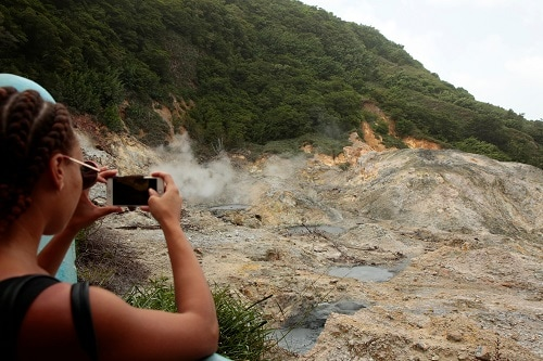 girl taking a photo of the mountains in st. lucia