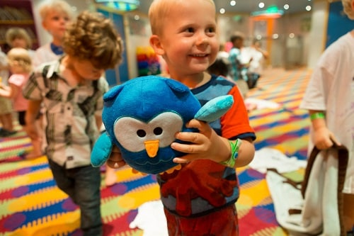 little boy happily holding a plush blue owl