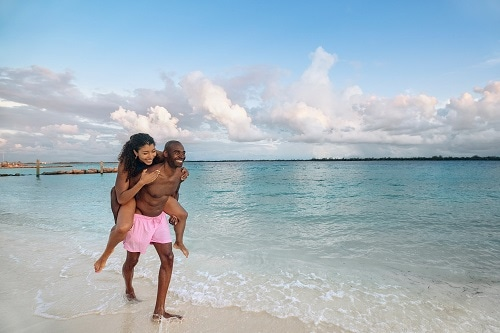 man running down the beach while carrying his significant other on his back