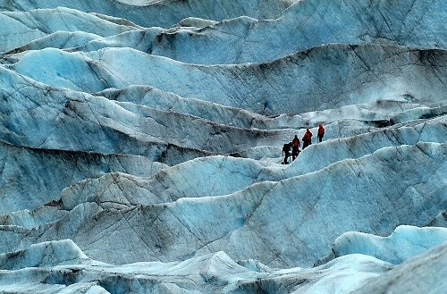 travelers hiking to an alaskan glacier
