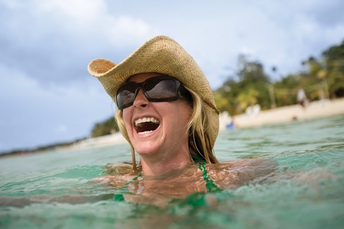woman wearing a hat and sunglasses while laughing at the beach