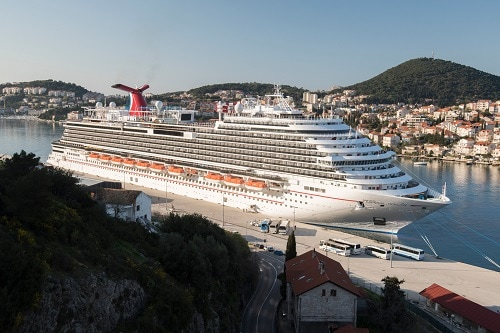 a carnival ship pulling into the port of dubrovnik