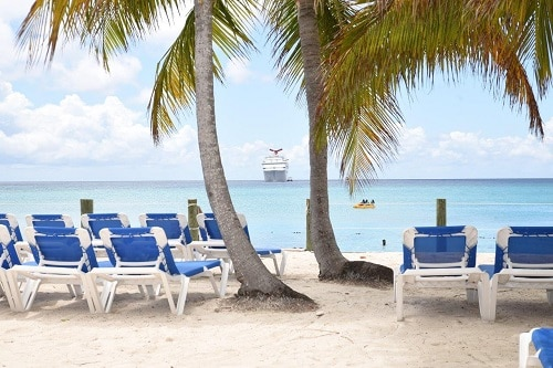 a carnival ship pulling up to a beach with palm trees and chairs in princess cays