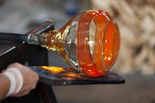a glassblower crafting a bottle in italy