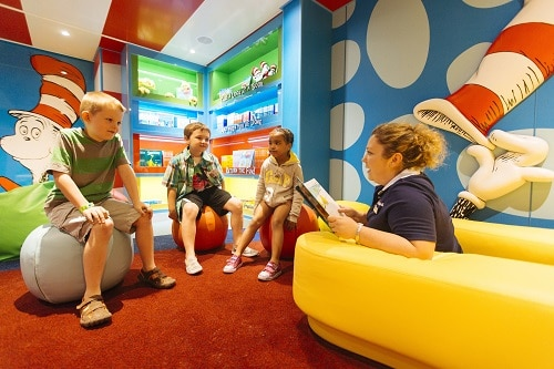 a group of children gathered around to read a dr. seuss story