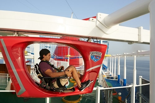 man paddling through the skyride onboard a carnival ship