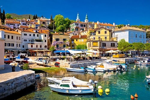 the marina of opatija with boats and the village in the background