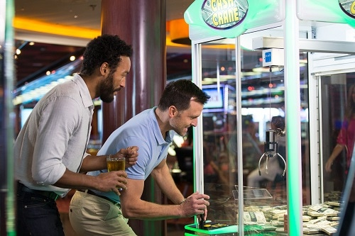 two friends playing the cash crane in the casino