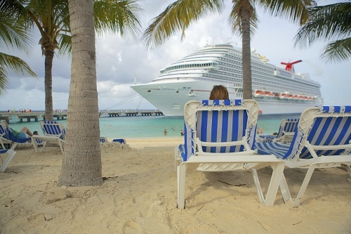woman on the beach watching a carnival ship pull in port