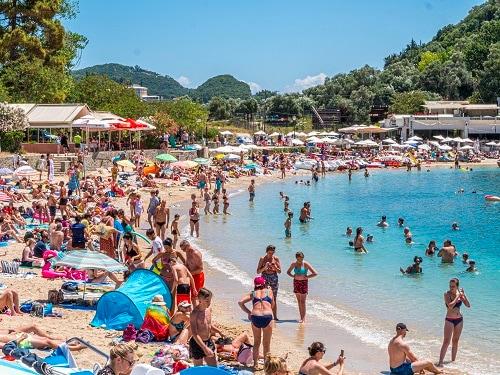 a beach full of travelers at paleokastritsa in corfu