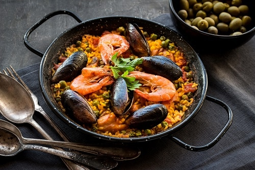 a black paella pan with fresh seafood paella served on it