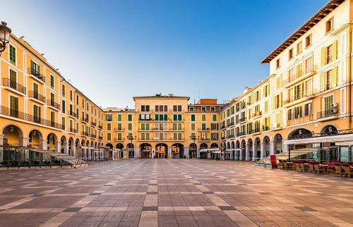 a bright yellow building and the tile courtyard that makes up plaça major in palma de mallorca